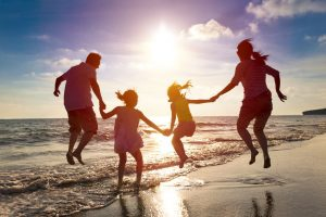 41118428 - happy family jumping together on the beach